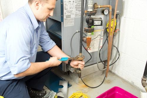 heating hvac technician repairing heater